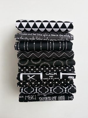 10 black and white fabrics in a stack