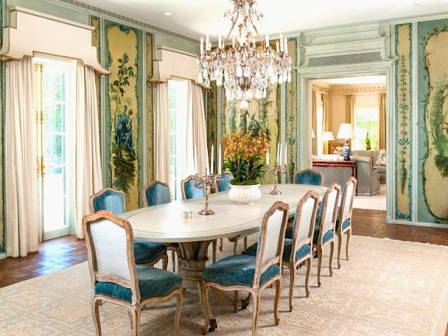 Dining room in a Palm Beach estate with crystal chandelier, custom Trompe-l'oeil painted walls, wood floor and blue velvet upholstered chairs