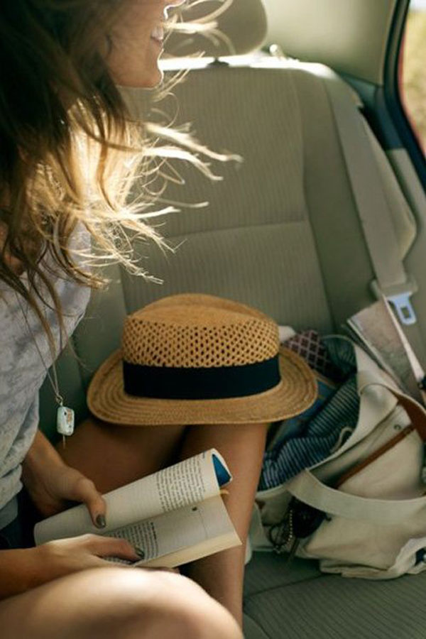 girl reading on a car