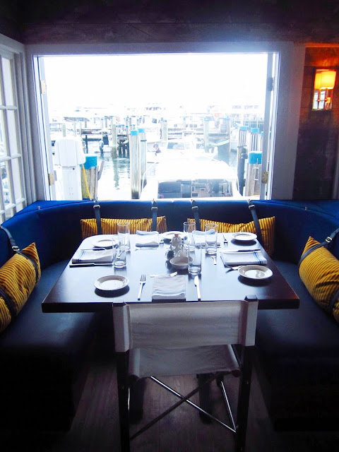 a booth with blue bench seating and yellow striped pillows attached with  buckles