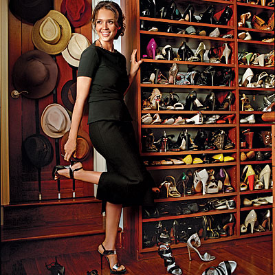 Jessica Alba in her closet with wide-brimmed hats hanging down the left side and shelves of shoes on the right.