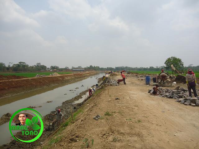 Pemasangan batu penahan tanah bibir saluran sungai Bendungan Macan.