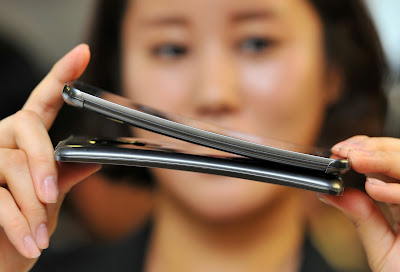 An official shows a Plastic OLED (POLED) display used in LG Electronics' curved-screen smartphone G Flex during a media event to unveil the new product at the company's headquarters in Seoul on November 5, 2013. The G Flex has a 6-inch plastic OLED display that curves inward from top and bottom. The device will hit the market in South Korea next week