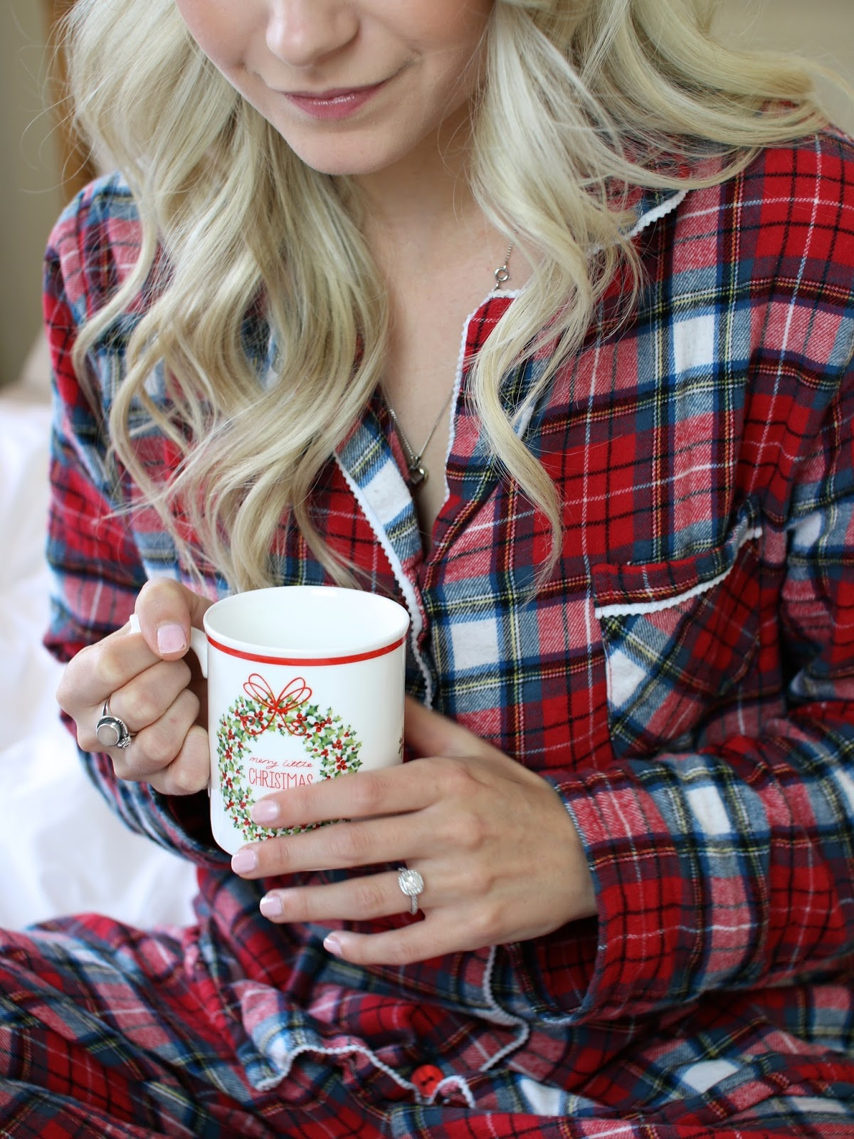 blonde women cozy in red and green PJ's with a cup of hot coffee