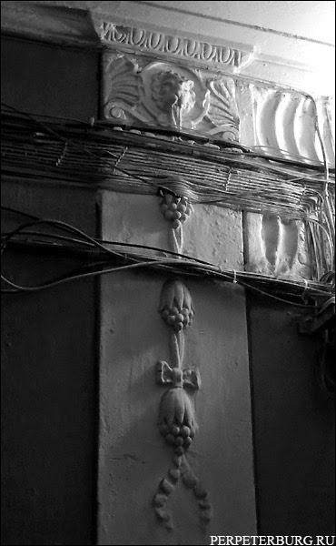 Лепнина в питерской парадной над дверью. Морды львов