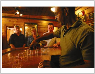 a tour guide pouring a sample of bourbon for some guests at buffalo trace distillery