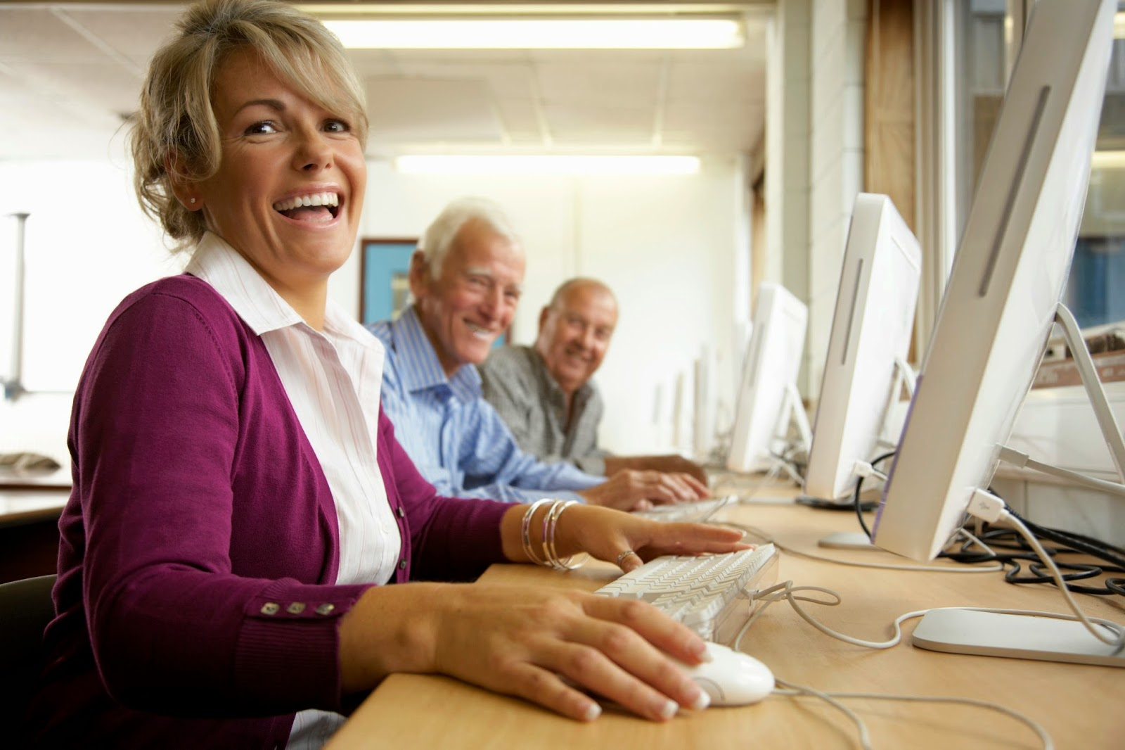 Image of three senior adults using computers