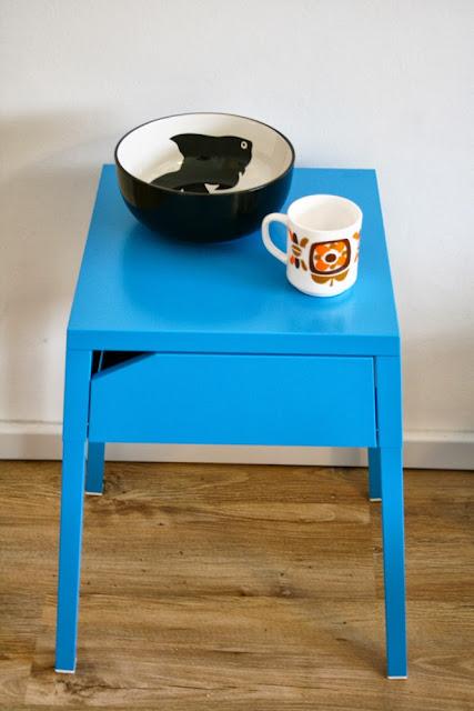 Table de chevet bleue, saladier noir, tasse Mobil
