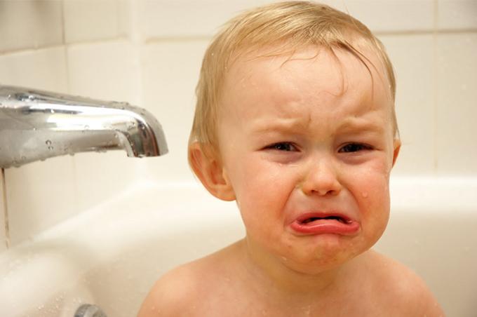 صورة طفل يبكي في داخل حوض الاستحمام بجانب صنبور المياه