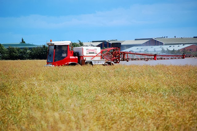 Photo of farm vehicle spraing a field of crops
