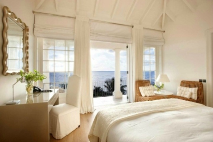 Coastal white and rattan bedroom with ocean view