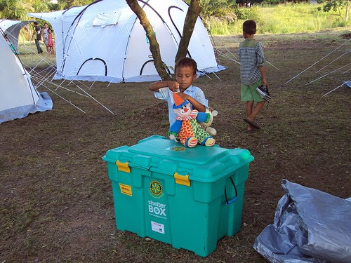 A picture of a child standing behind a Shelterbox box