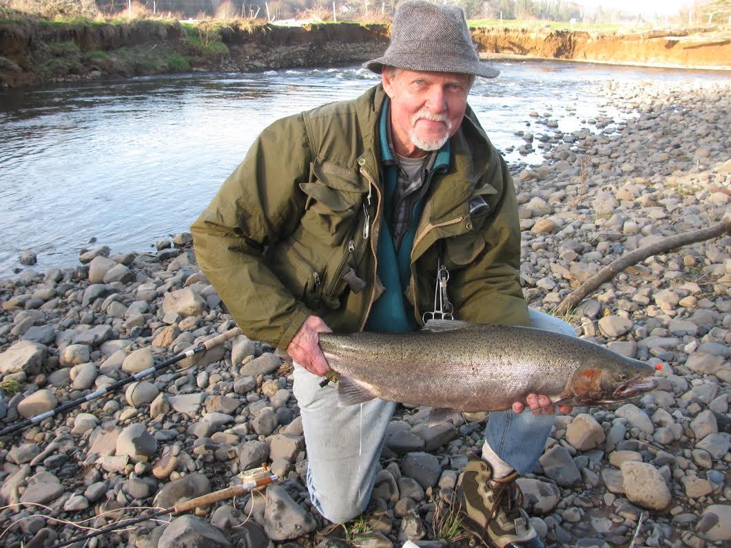 Doug Stewart holding a 12 to 14 pound winter steelhead on rocky bank of  a small stream.