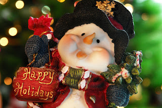 Merry Christmas snowman smiling with carrot nose and cap on head and holding happy holidays craft in hand, X ams tree lighting decoration background wallpaper