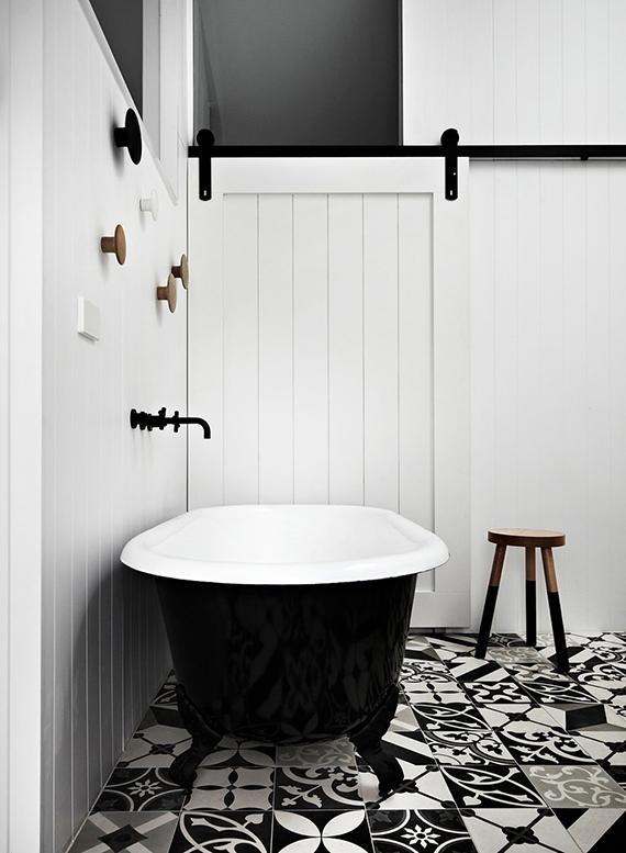 Black fixtures in the bathroom | B&w cement floor tiles and a black bathtub in this bathroom designed by Whiting Architects.