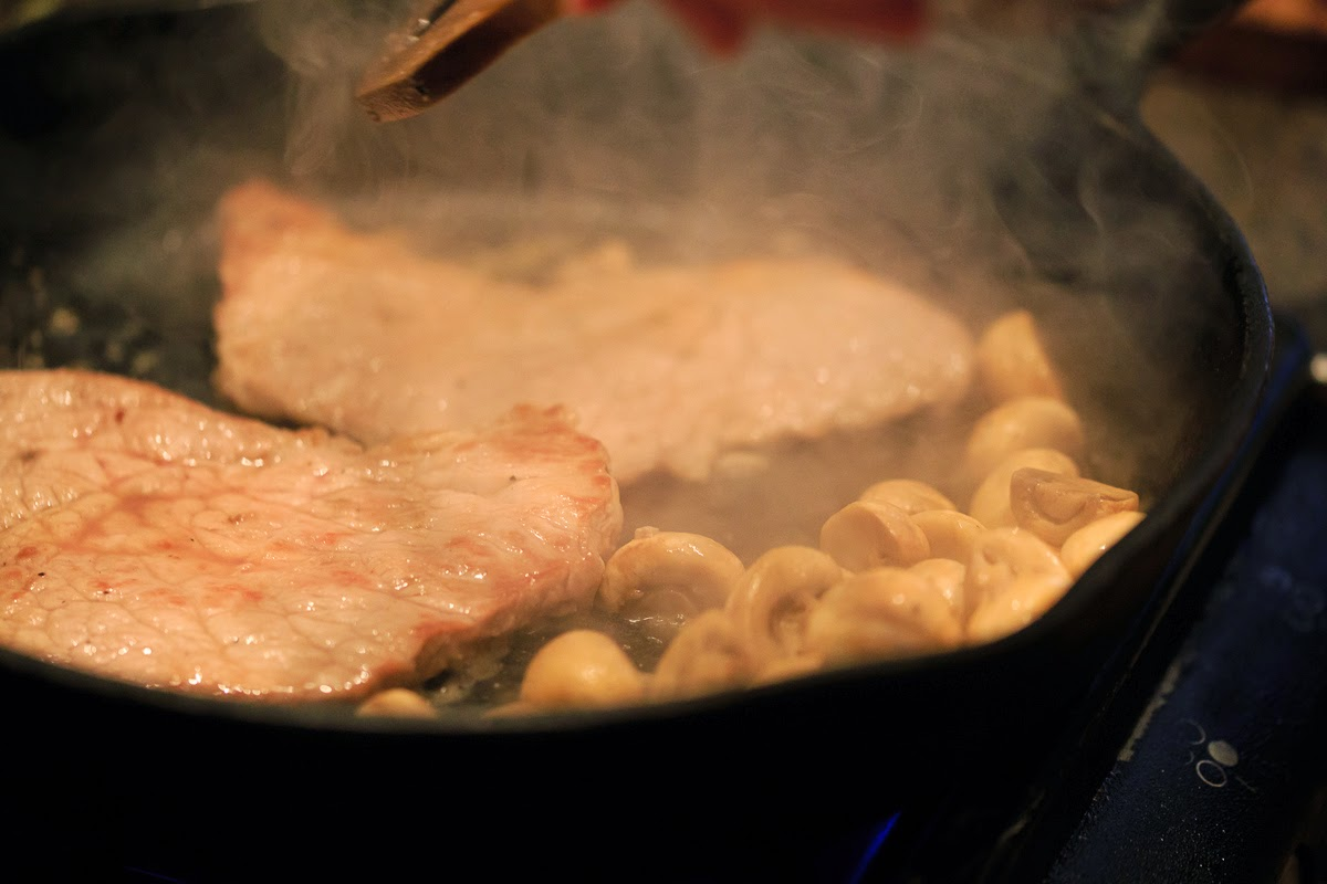 Veal and mushrooms frying in a cast iron pan