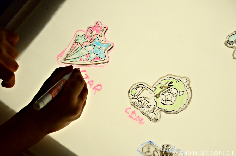 Writing and labeling dollar store sun catchers on the light table from And Next Comes L