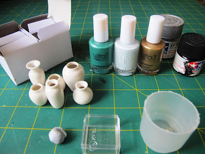 Slection of dolls' house miniature white vases, bottles of nail varnish and paint and plastic containers on a cutting mat.