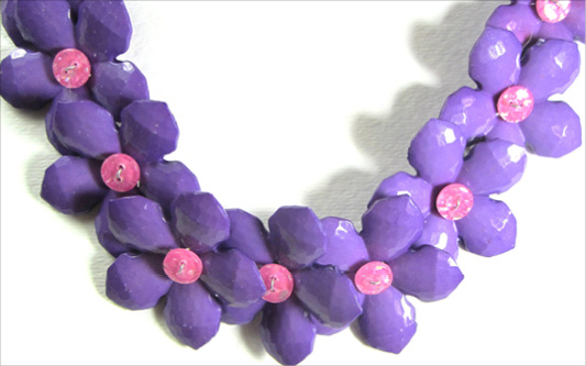 Colorful necklace has big bold purple flower buttons with smaller pink flower buttons