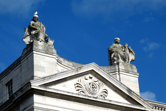the roof of a government building with statues and a pigeon on one of their heads