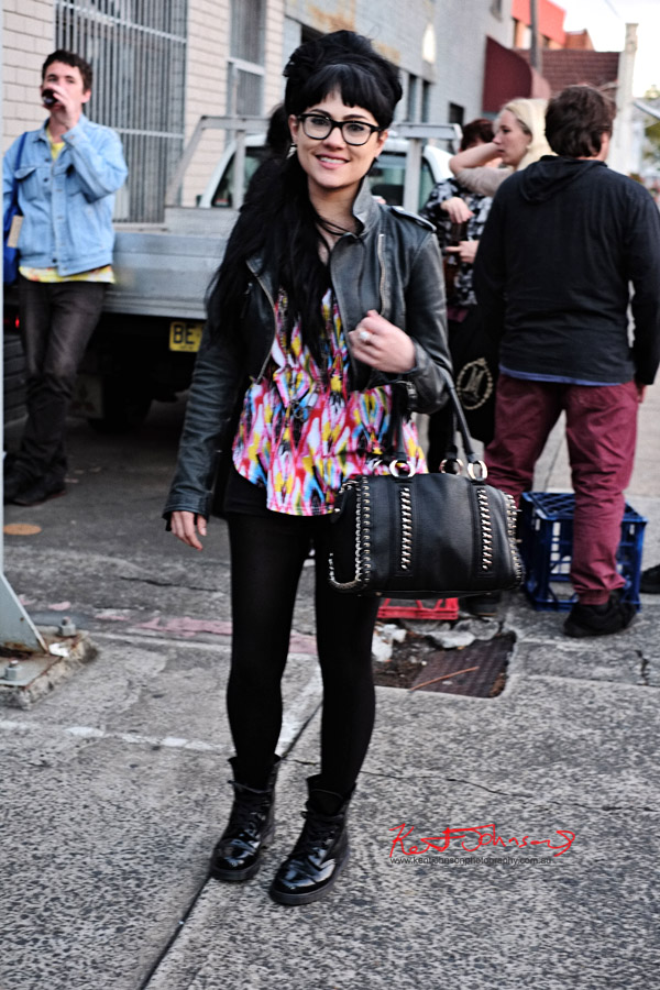 Street Fashion Sydney - Black leather jacket tie-dye shirt black leggings boots and hipster glasses, 60's retro style - full length shot