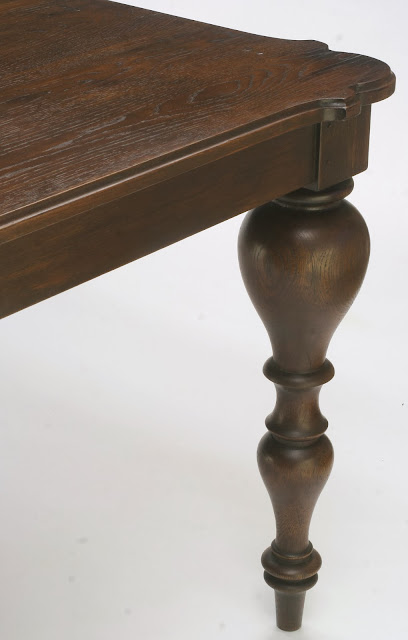 solid oak extension dining table with antique walnut finish has dramatic turned legs