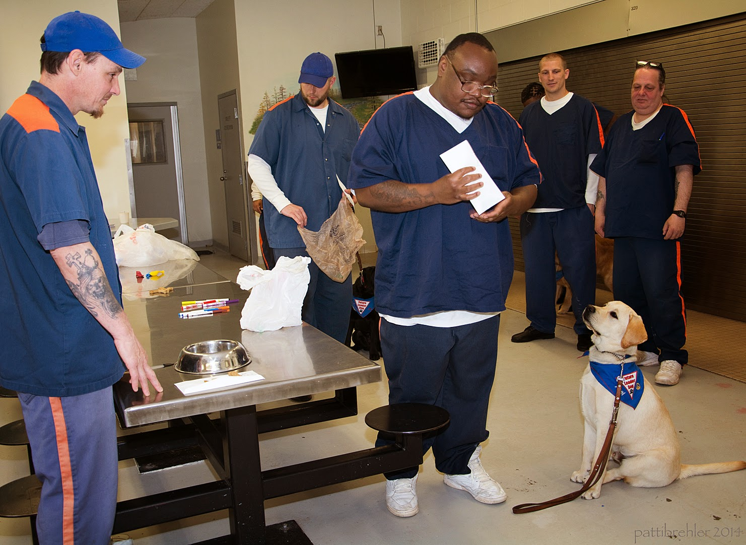 Five men dressed in the prison blue uniforms stand arond a steel lunch table. The man on the left, wearing a blue baseball cap, has his fingertips on the table with a silver stainless steel dog bowl in front of him on the table. The afrcan american man standing opposite him is looking down at a white envelope in his hands. A yellow lab puppy is sitting to his left looking up at him. The puppy is wearing the blue Future Leader Dog bandana and his leash is hanging on the ground. Three men in the background are watching the dog. There are white plastic shopping bags on the table.