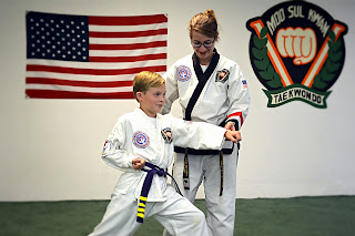 Martial arts black belt instructor teaching leadership in kid's karate class