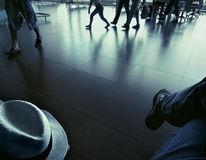 Vária pessoa a andarem rápido, ao longe e um chapéu e uma perna em primeiro plano
