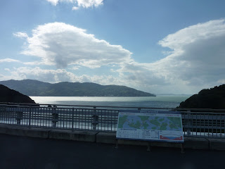 View from the Omichima bridge on the Shimanami Kaido bikeway with the Seto sea and islands in background and information plaque in the foreground