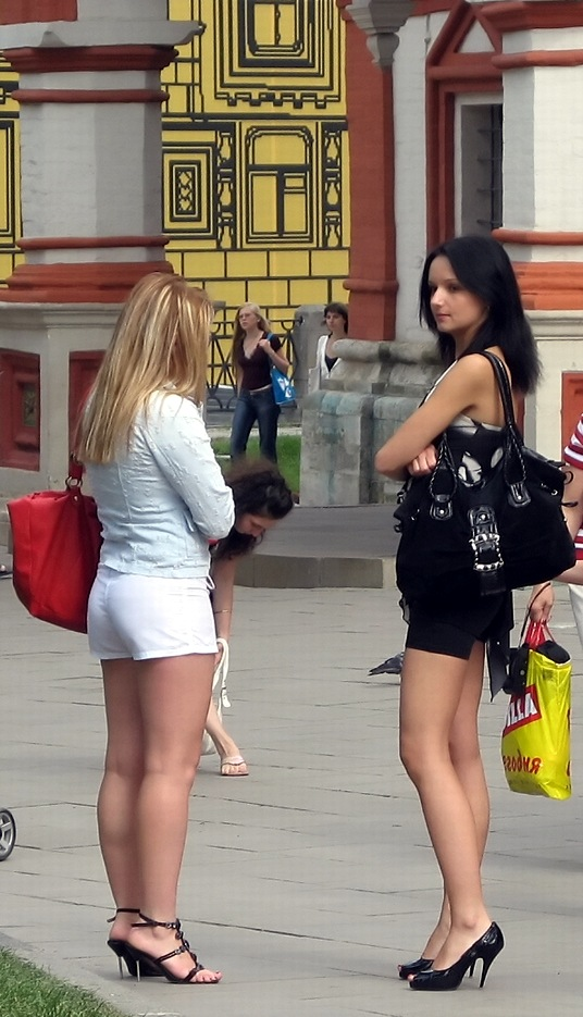 Blonde in white and brunette in black on high heels