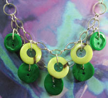 Plunging necklace has double layers of green fashion buttons hanging pendant style from strands of silver chain