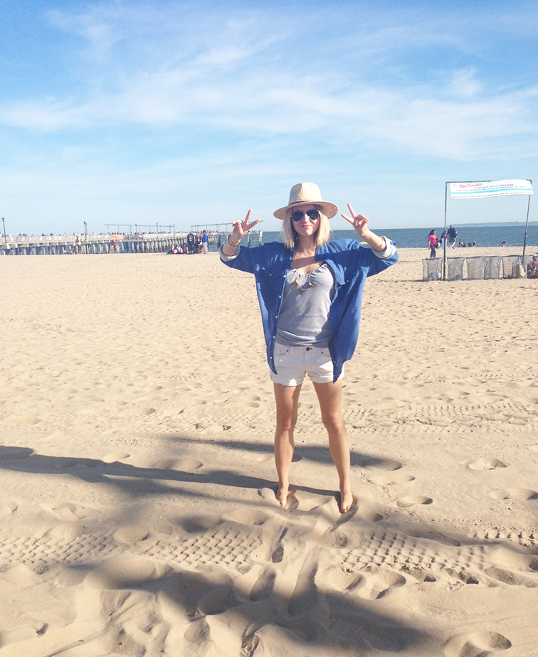 Coney Island beach, on the sand, peace sign, pastel colors, relaxed, casual attitude