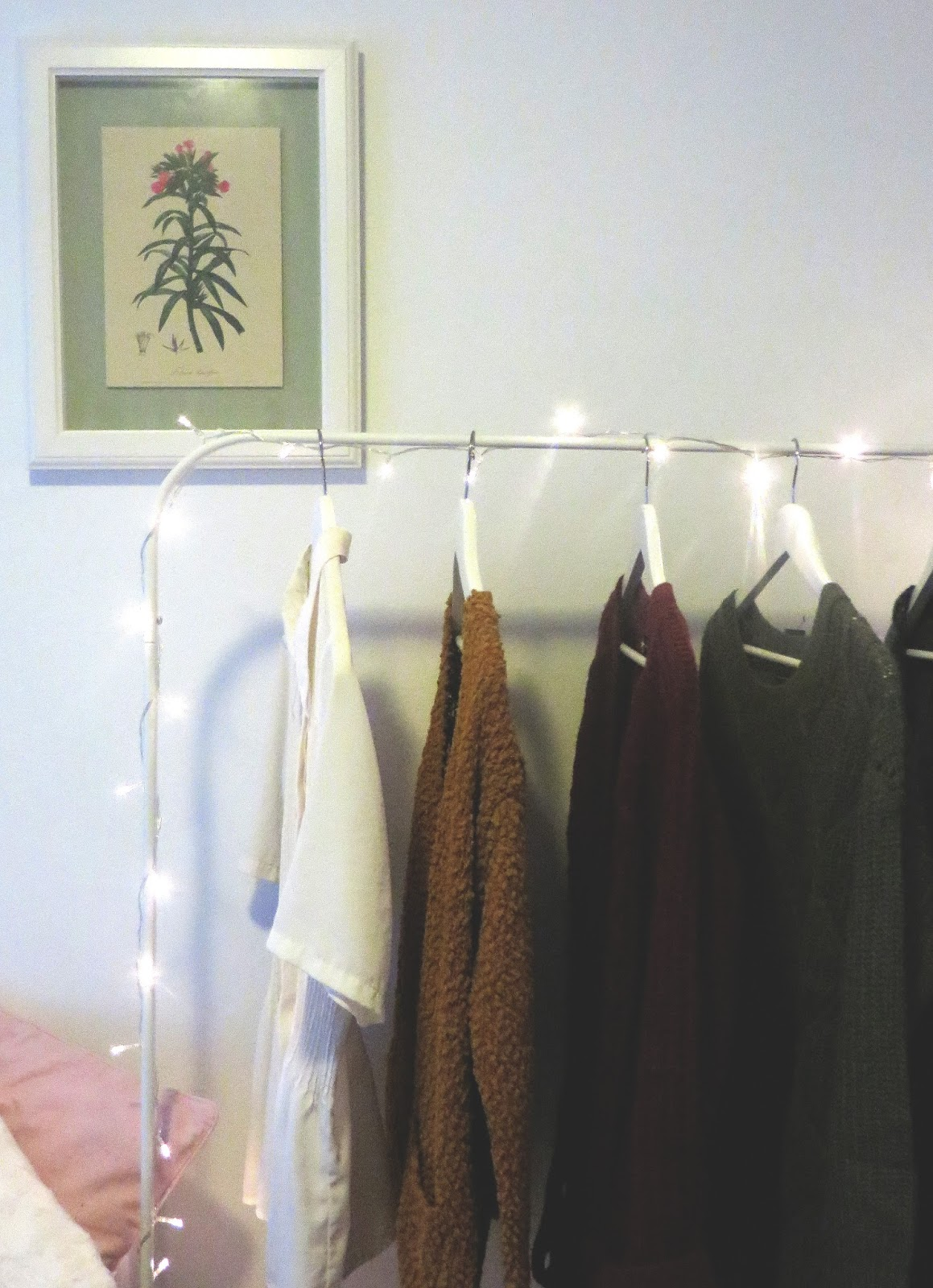 clothing rack with fairy lights and a painting