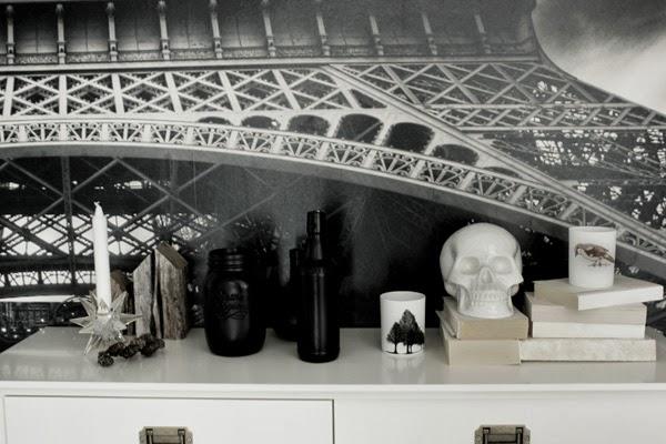 döskalle, vit porslin skalle, inredning, stilleben, avlastningsbord, vitt bord med stilleben, inreda med böcker, bygga på höjd med böcker som dekoration, ljusstake, svartsprayade flaskor, trärena hus, photowall, mr perswall, em möbler bord, fototapet