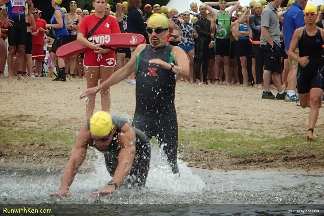 Up-close action photo of triathletes LEAPING into the open water at the Triathlon at Lake Pearl in Wrentham, MA. Sports Photography from Inside the Pack by Ken Skier, the Swimming Photographer. (RunwithKen.com) The Triathlon at Lake Pearl is produced by the Hockomock Area YMCA.  (hockymca.org)