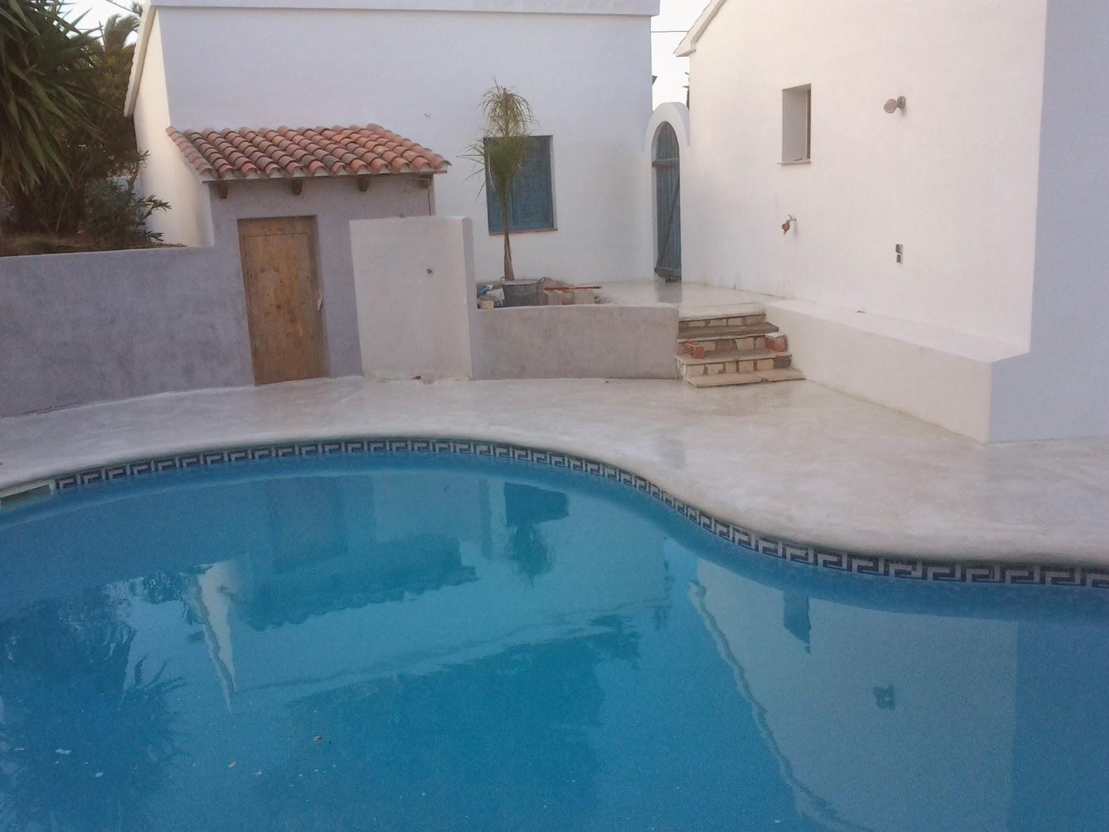 Piscina con pavimento continuo de hormig n en color blanco for Precio de piscinas de cemento
