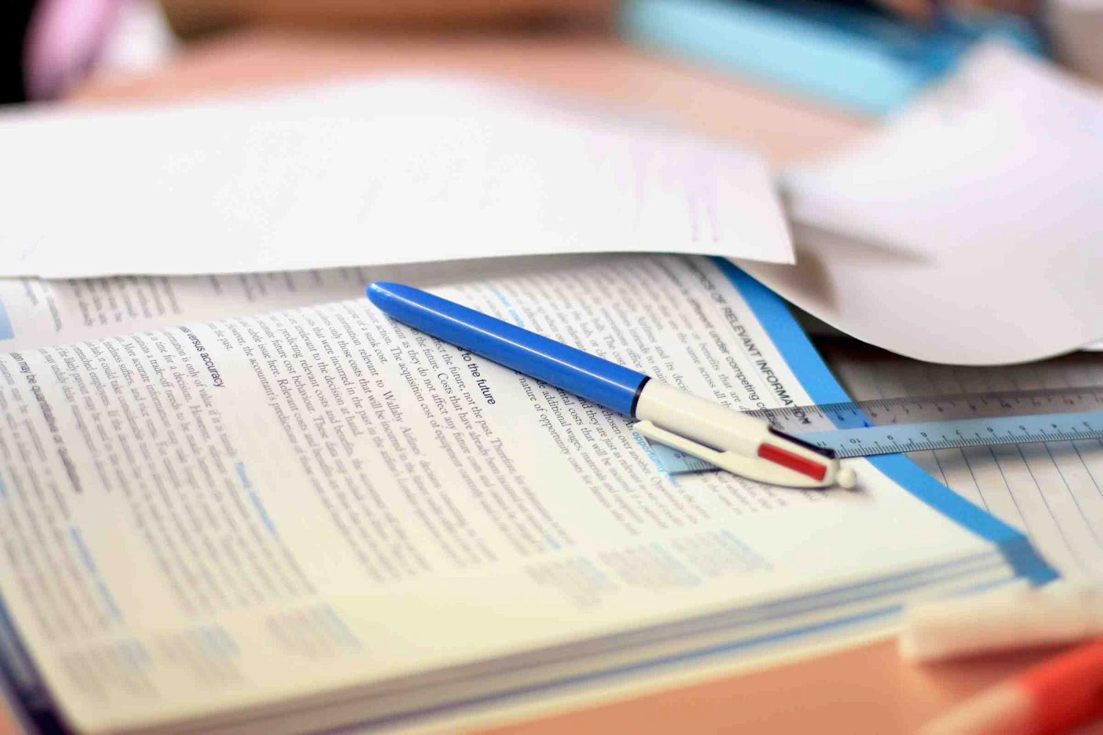 Taula d'estudi amb un llibre obert i un bolígraf