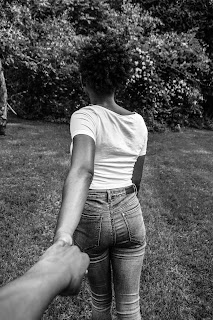 black and white image of young black woman leading photographer by the hand across a yard