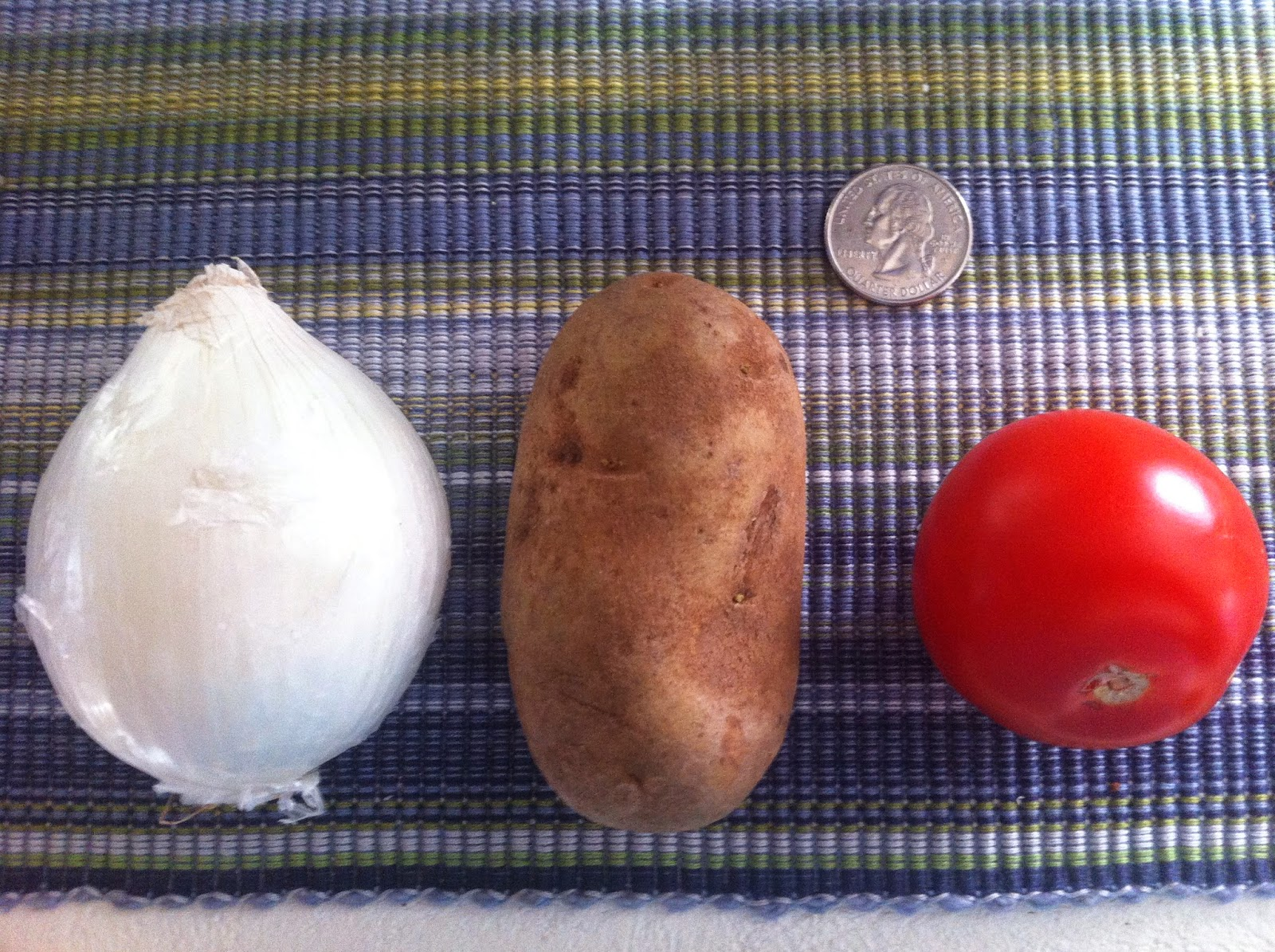Small onion, potato, and tomato next to a quarter for scale