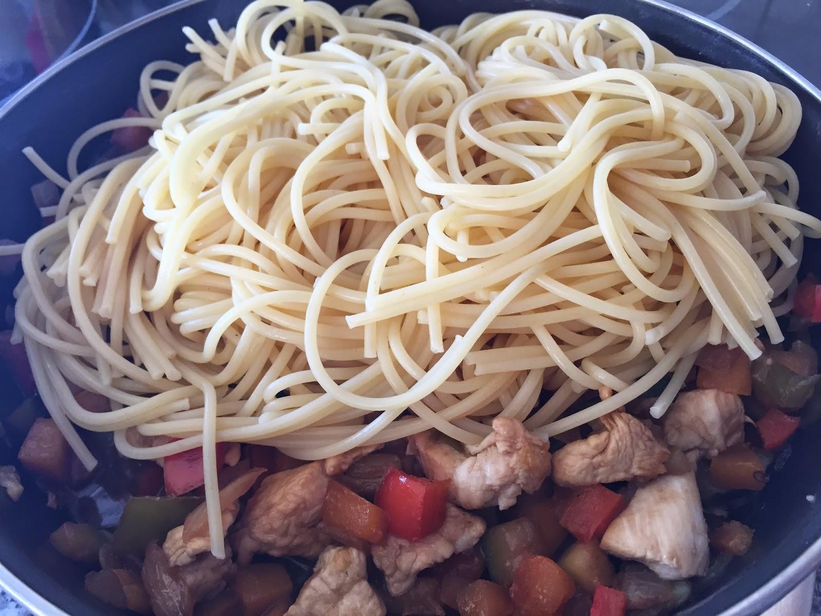 Espaguetis con verduras y salsa de soja, añadiendo los espaguetis.