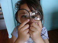 Little girl looking through two magnifying glasses