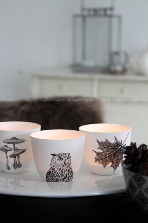 Herbstimpressionen mit drei Teelichtern mit Eulen, Pilz und Herbstblatt Motiv vor einer Kommode mit Kürbissen
