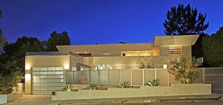 Street facade of Modern Beverly Hills House with open interiors at night