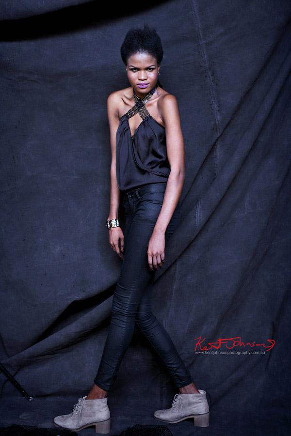 Black black model against black backdrop in black jeans and top.