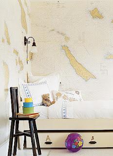 quarto solteiro com duas paredes com mapas adesivados, tons bem claro que não pesam na composição