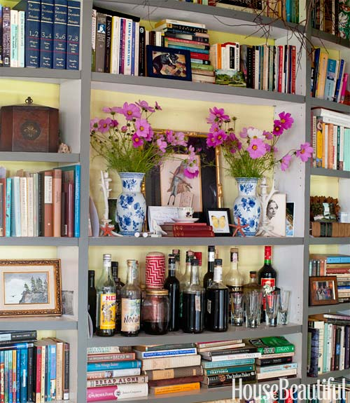 house beautiful's built in bookshelves stuffed full of books, larger shelves hold items like flower arrangements, a small bar and other trinkets