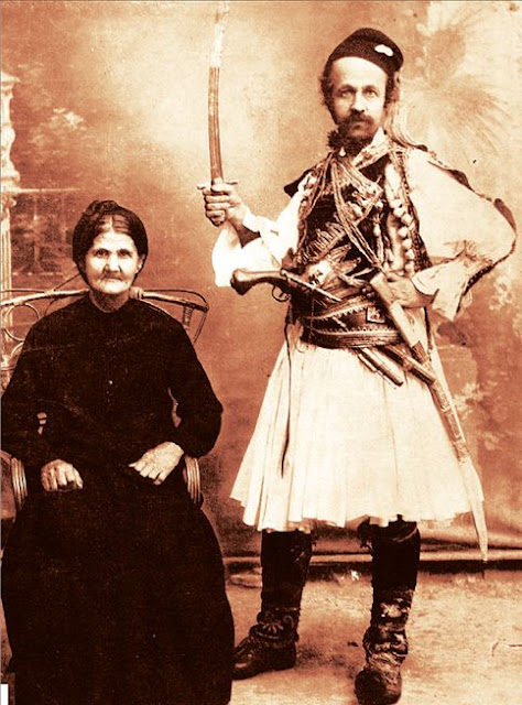 Theofilos is photographed beside his mother, wearing the pleated skirt and girded with weapons, with a sword raised, as a hero of the Revolution
