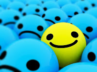 One bright yellow smiley face around sad blue ones.