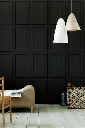 Dark living room with black paneled walls white pendant light grey wood floor